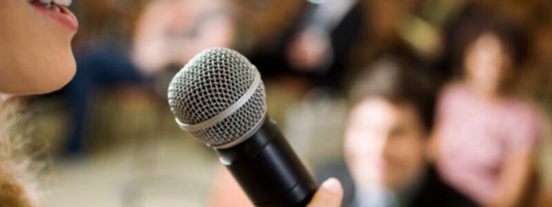 Her ser du en kvinde med mikrofon. Find færdige festsange her på siden.