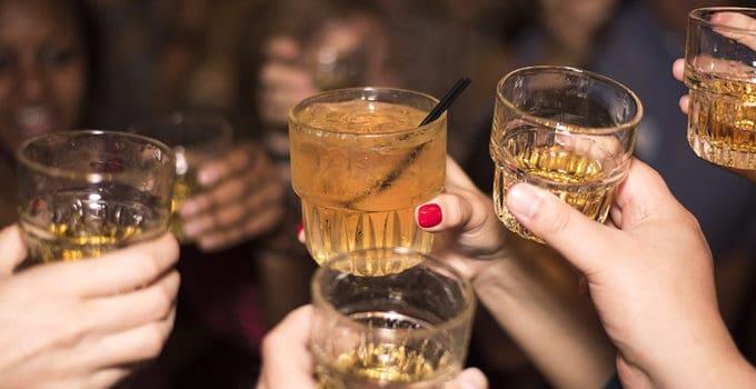 Folk skåler med velkomstdrinks til firmafest