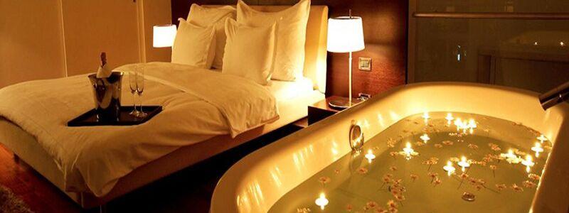 Romantisk miniferie illustreret ved at spabad og en seng med champagne på